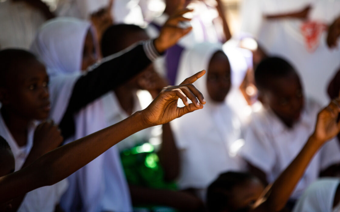 Students raising their hands to answer a question