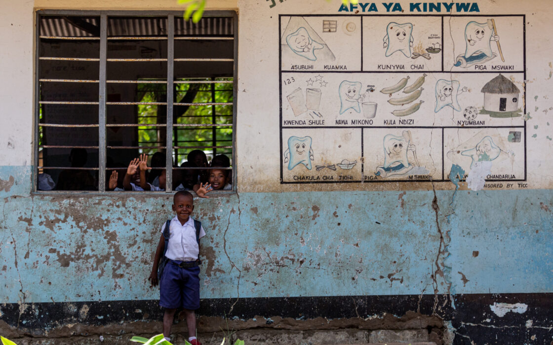 Boy in front of wall with a tooth program