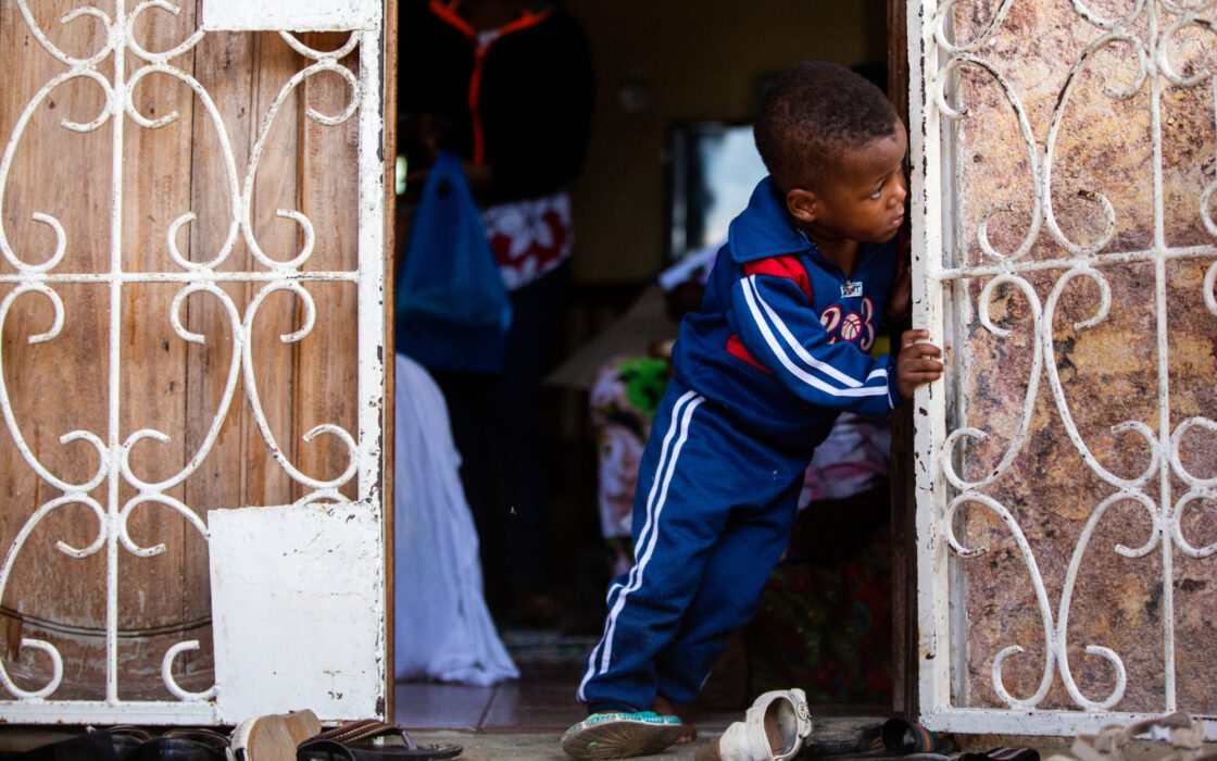Child peeking out of the family home while leaning on the door