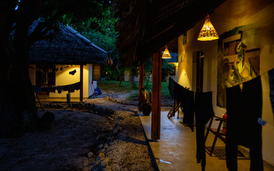 Two bungalows at night, with dim lights at their entrances