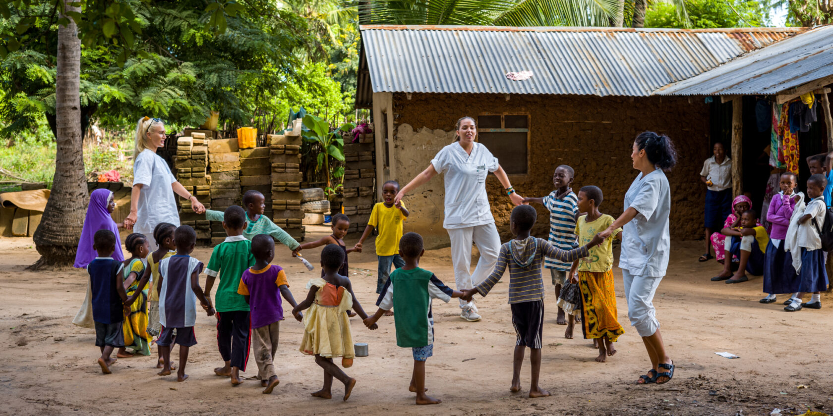 Students and children forming a circle by holding hands, spinning around and singing