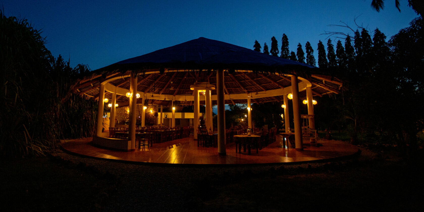 The makuti roof with the dining place beneath alit in the night
