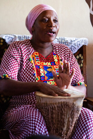 Woman singing and playing drums in a song session in the family home