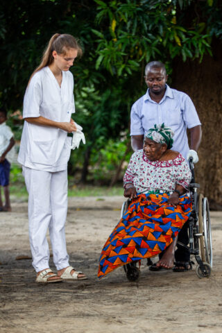 Student preparing to take care of an elderly woman in a wheelchair