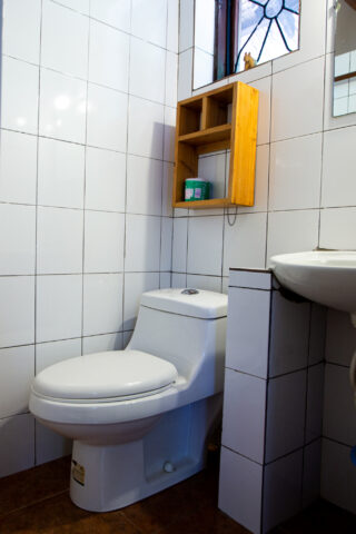 A clean toilet in a clean bathroom with a window
