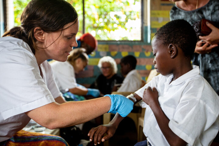 Student applying a bandaid to a wound on a childs arm