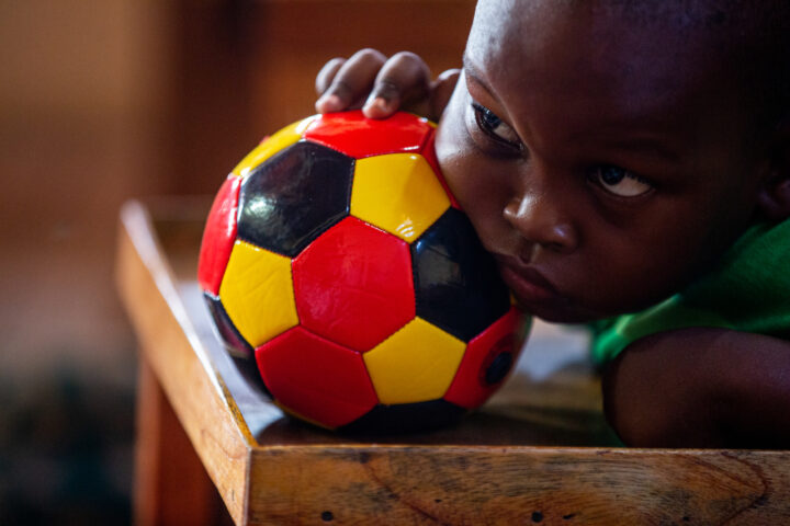 Child paying attention while holding a football
